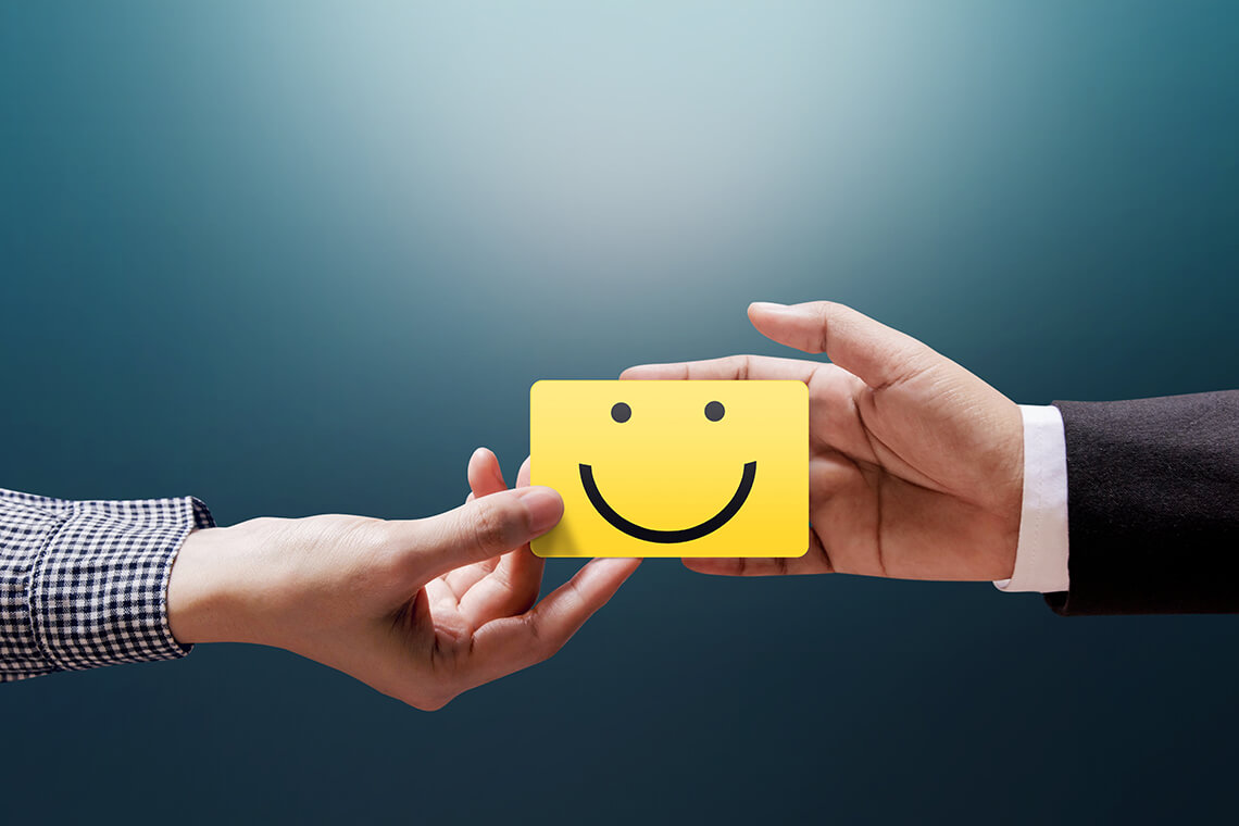 Customer giving Happy Smiley Face Card into a Hand of Businessman
