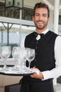 Smiling waiter with tray